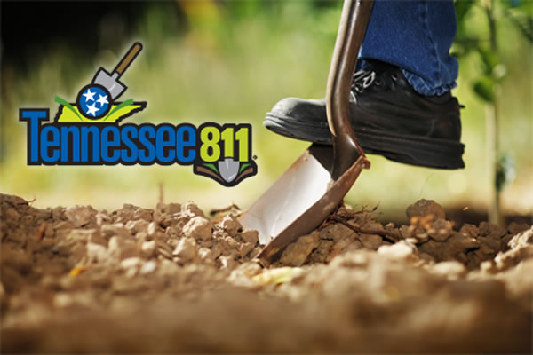 A shovel is being pressed into the soil by a person wearing a brown leather boot. Only the ankle and boot are visible on the person. Brown, tilled, soil fills the foreground. A Tennessee 811 logo is overlaid to the top left of the image.