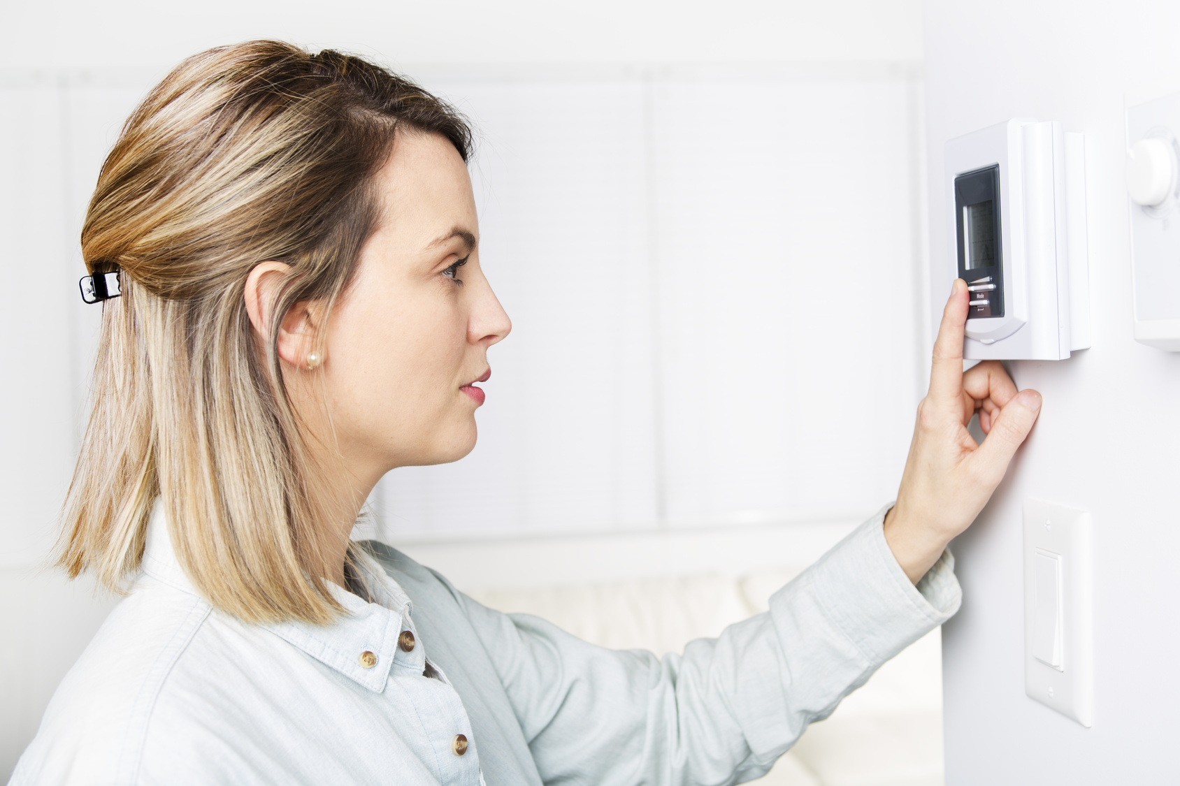 Blonde woman in white shirt changes temperature on electric thermometer.